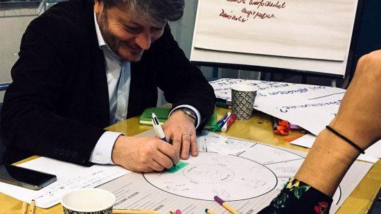 Les participants en train de dessiner sur le centre du plateau de jeu